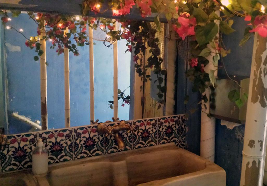 VIVA LA VIDA-baño del restaurante vegetariano con una gran pila de piedra, adornado con flores y guirnaldas de luces